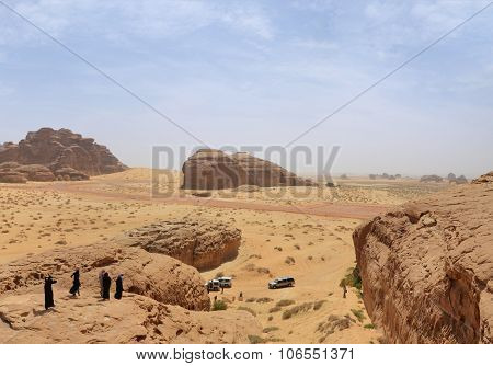 Group of people on a tour in desert landscape - red mountains blue sky poster