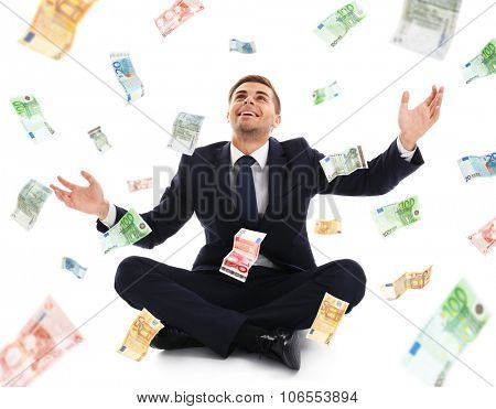 Businessman sitting on case in the rain of money