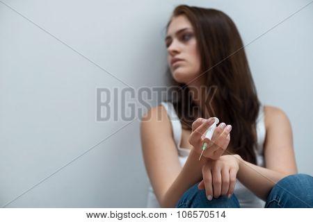 Drug addict sitting on the floor