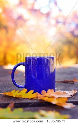 Blue Cup On Wooden Table With Autumn Blurred Background
