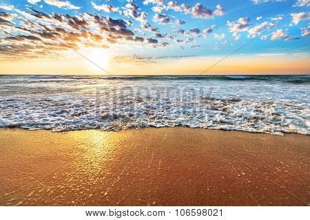 Colorful Ocean Beach Sunrise With Deep Blue Sky And Sun Rays.