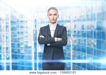 Female executive with hands crossed, blue background. Concept of leadership and success