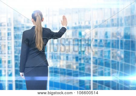 Backview of businesswoman waving her hand to background. Concept of leadership and success