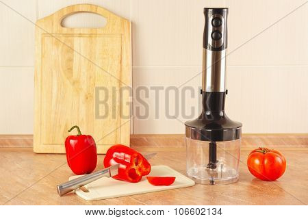 Chopped red bellpepper with tomato and a blender on kitchen table