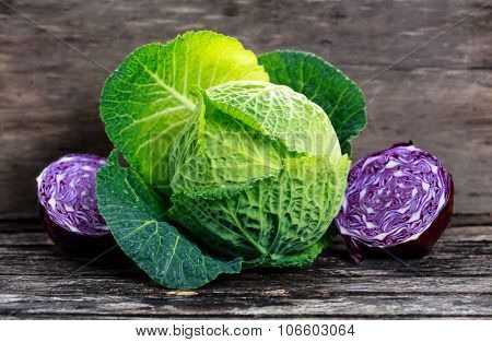 Fresh  Green Cabbage And Slice Of Red Cabbage On Old Wooden Table