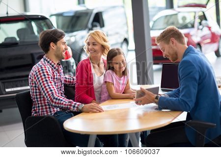 Car salesperson demonstrating new automobile to young family