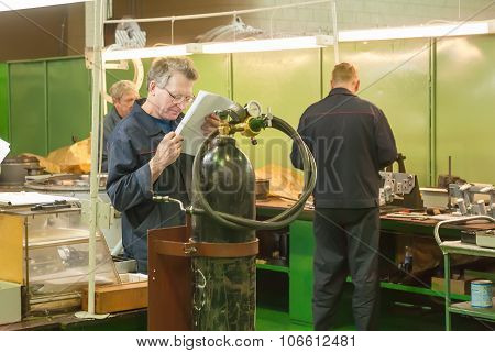 Elderly mechanic reads drawing in shop