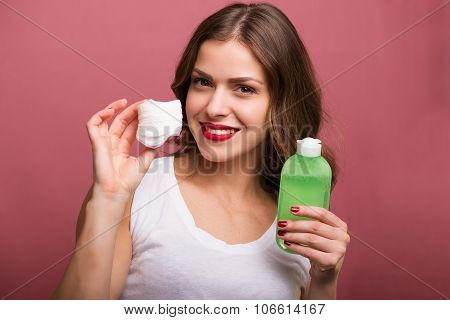 Woman cleaning her face with a lotion and a cotton pad poster
