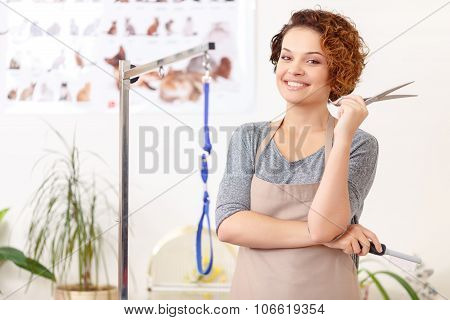 Smiling groomer with her work utensils.