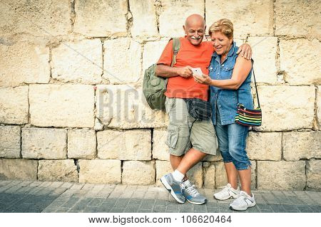 Happy Senior Couple Having Fun With A Modern Smartphone - Concept Of Active Elderly And Interaction