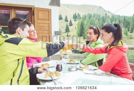 Group of friends toasting with beers. four people having lunch outdoor. winter background with mountains and trees poster