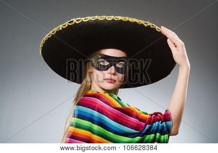Girl in mexican vivid poncho against gray poster