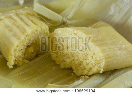 Closeup of unwrapped traditional Brazilian sweet corn dumpling on corn husks poster