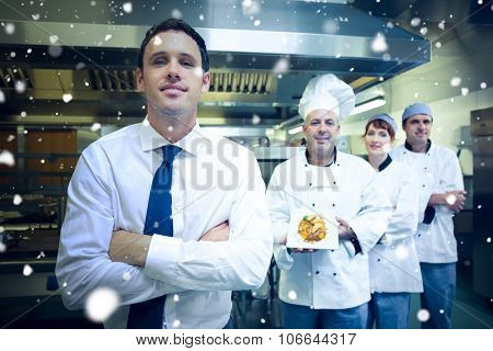 Snow against young restaurant manager posing in front of team of chefs