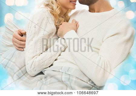 love, family, winter and happiness concept - close up of happy couple cuddling under paid at home over blue lights background