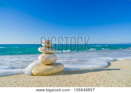 Stones balance, pebbles stack over blue sea in Croatia. Blue sky on sunny adriatic coast in summer.