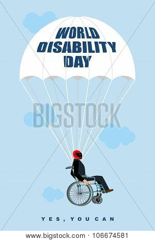 World Disabilities Day. Man In  Wheelchair Goes Down On Parachute. Disabled In Protective Helmet Fli