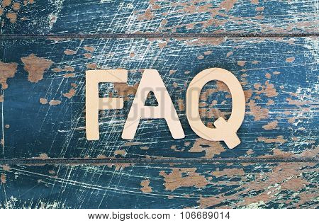 Word FAQ written on rustic wooden surface