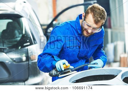 auto mechanic worker  polishing bumper car at automobile repair and renew service station  by power buffer machine