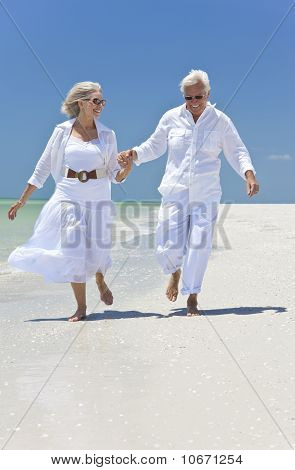 Happy Senior Couple Running Holding Hands On A Tropical Beach
