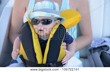 Mother holding baby with lifejacket on that needs to be zipped up with sunglasses and hat