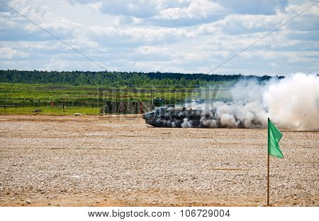 A lit tank MT-LB in motion