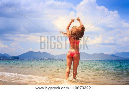 Blonde Slim Gymnast In Bikini Stands Backside On Edge Of Sea