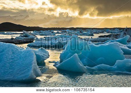 Icebergs from Vatnajokull are melting at Jokulsarlon glacier lagoon and floating to Atlantic ocean at summer sunset, Iceland poster