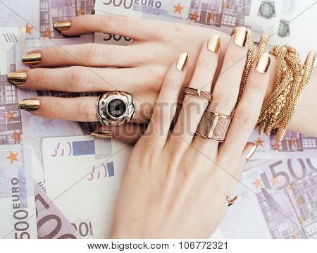 hands of rich woman with golden manicure and many jewelry rings on cash euros close up
