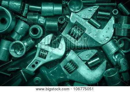 Grange background with wet tools and bolts. Adjustable wrenchs screws nuts. Toned. poster