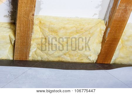 Wooden Beams Of Attic With Thermal Insulation Fitting In There And Foil