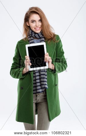 Portrait of a smiling woman showing blank tablet computer screen isolated on a white background
