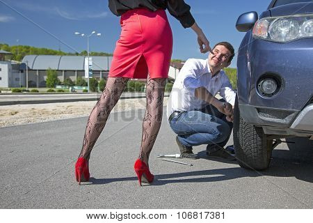 Leggy female body sexy stockings pointing her hand towards car wheel to be fixed by conformable man roadside outdoor sunny day blue sky poster