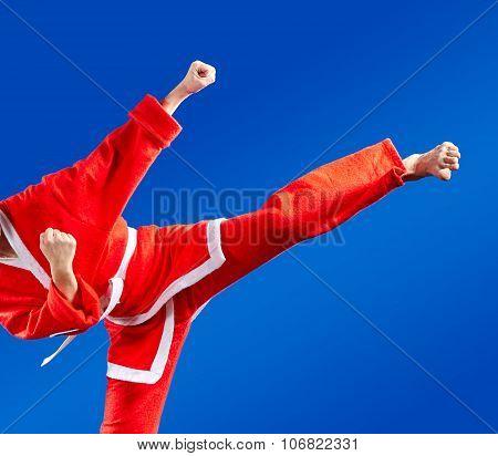 Sportswoman dressed as Santa Claus hits a high kick