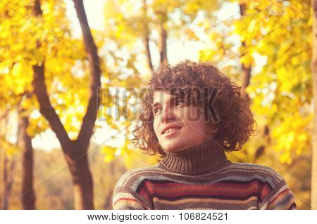 Portrait of happy smiling attractive man dressed in striped sweater, oudoor in autumn park.