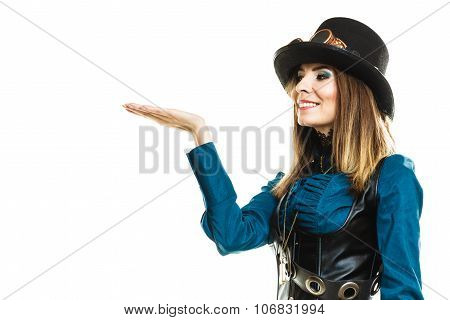 Smiling young steampunk islolated girl on white holding fancy rifle with open hand plam. Fantasy old fashion wearing hat and goggles. poster