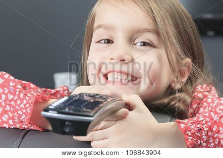 A cute little girl with remote control in front of TV. poster