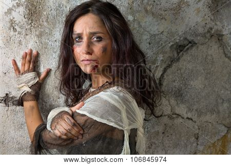 Homeless young woman dressed in rags in a derelict building