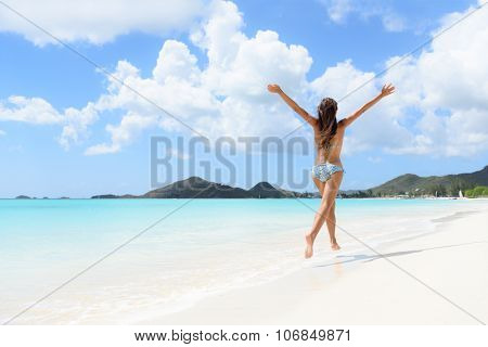 Beach, travel and vacation holidays concept with bikini girl happy running full of joy and aspiration on pristine beautiful Caribbean beach with turquoise water. Woman on Jolly Beach, Antigua. poster