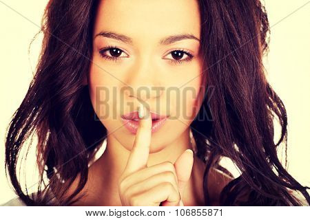 African woman making a hush gesture.