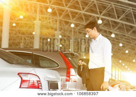 Indian business man at car park, holding car remote key.