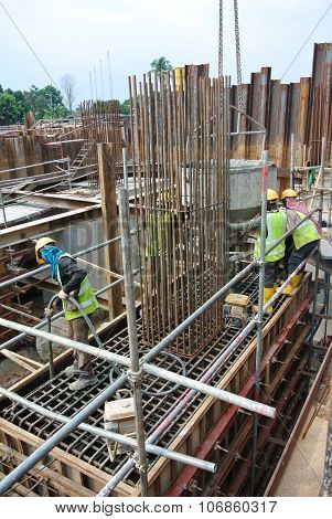 Construction Workers Using Concrete Vibrator to compact the concrete slurry