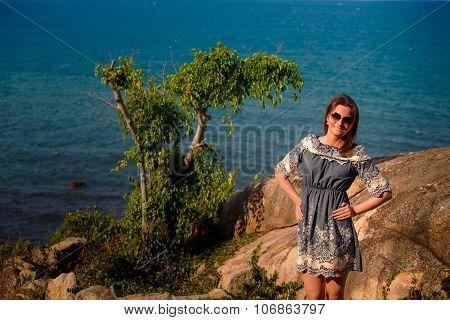 Brunette Girl In Grey Frock Stands On Rock Against Sea