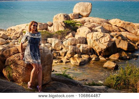 Girl In Short Grey Frock Stands On Rocks By Sea Against City