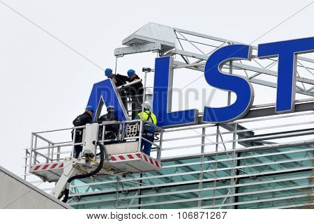 BADEN, SWITZERLAND. November 2nd, 2015. Workers remove the Alstom logo on rooftop of thermal power headquarters for merger and acquisition of General Electric.