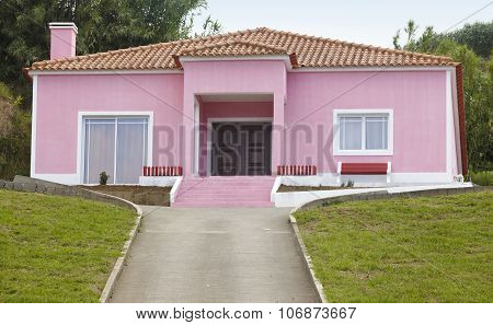 Pink House With Vehicle Entrance Way In Out And Garden