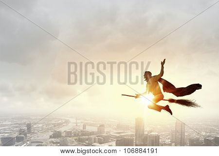 Young businessman flying high above city on broom