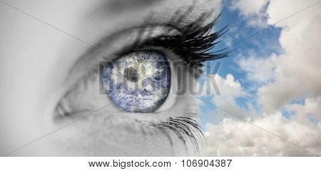 Blue eye on female face against blue sky with white clouds