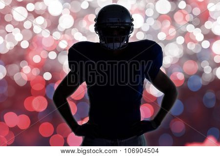 Silhouette American football player standing with hand on hip against glowing background