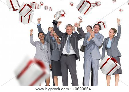 Excited business team cheering at camera with trophy against white and red gift box